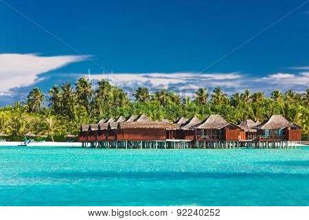 Overwater bungallows in blue lagoon on tropical island with coconut palm trees