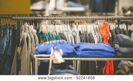 many hangers with different men's clothes in a shop