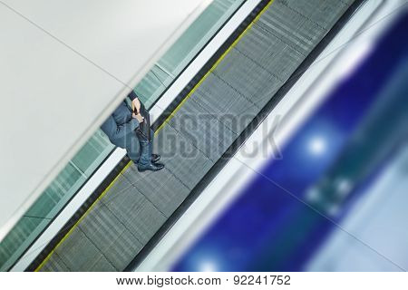 Legs of businessman with briefcase ascending on escalator