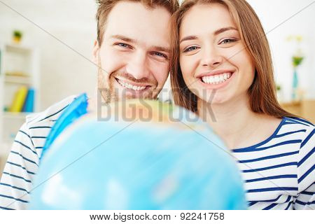 Amorous couple looking at camera with toothy smiles