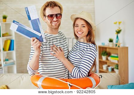 Young couple with airtickets looking at camera inside buoy