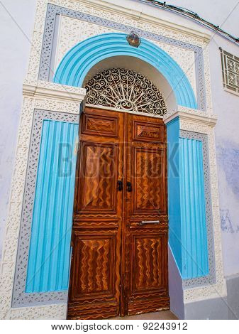 Ornate Carved Wooden Door Surrounded By Blue Stinework In The Medina In Kairouan, Tunisia