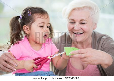 Senior woman with granddaughter cutting paper at home