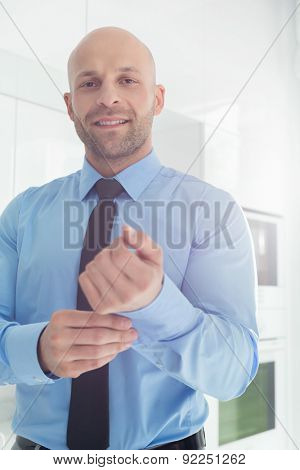 Portrait of mid adult businessman buttoning sleeve at home