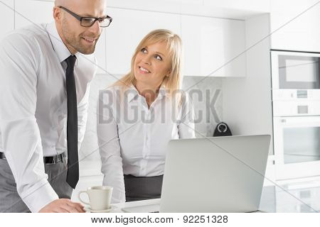 Happy business couple working on laptop in kitchen