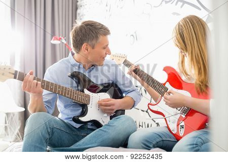 Middle-aged man with daughter playing guitars at home