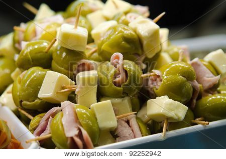 Tasty tapas with olives ham and cheese
