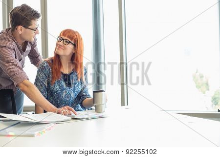 Businesspeople looking at each other while working at desk in creative office