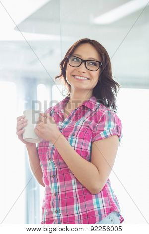 Happy businesswoman looking away while holding coffee mug in creative office