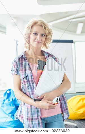 Portrait of beautiful businesswoman holding files in creative office