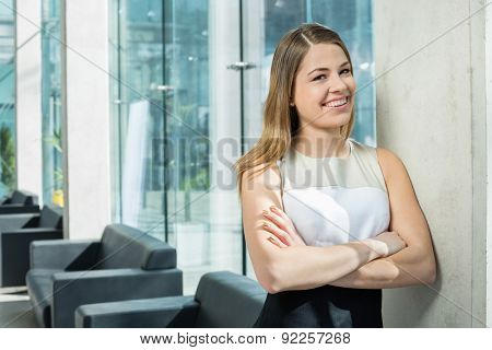 Portrait of happy businesswoman standing arms crossed at office lobby