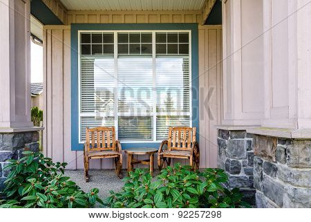 Front of a rustic house with a patio: two chairs and a table. Home exterior.