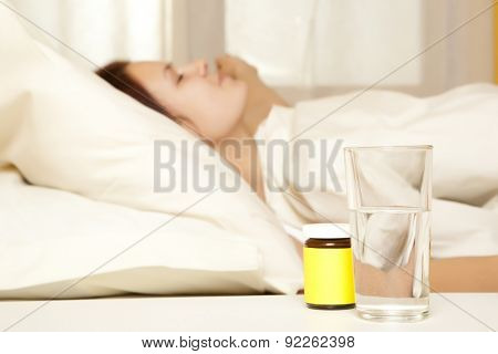 Female in bed at home caught cold, feeling bad, taking medicines, sleeping
