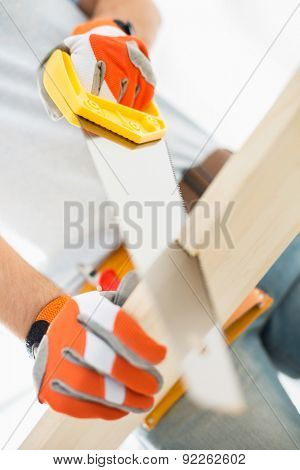 Midsection of man sawing plank