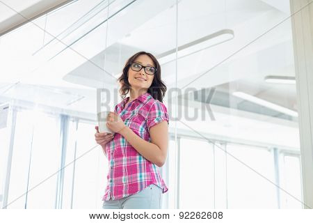 Businesswoman looking away while holding coffee mug in creative office