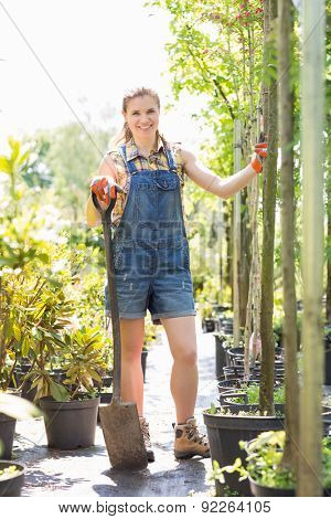 Full-length portrait of happy woman holding spade at garden