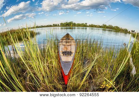 red canoe on a lake shore - distorted fish eye lens perspective, Fort Collins, Colorado