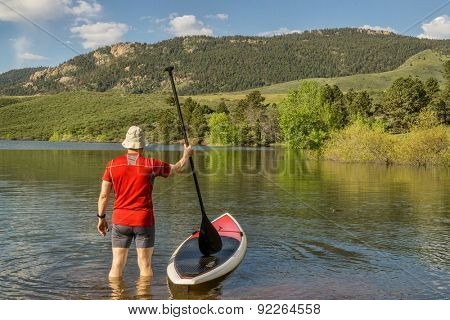 male paddler is about to step on his SUP paddleboard - a shore of Horsetooth Reservoir at foothills of Rocky Mountains, Colorado in early summer