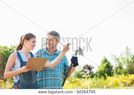 Happy female supervisor explaining something to gardener at plant nursery