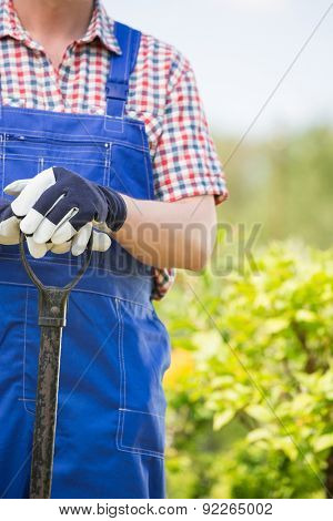 Midsection of man holding spade at garden