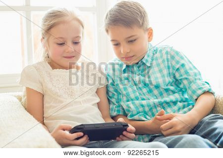 Siblings playing hand-held video game at home