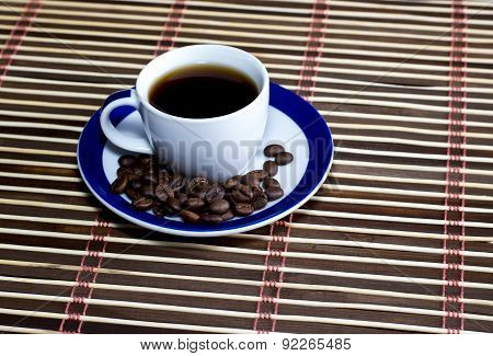 The Cup Of Coffee Strewed Around With Coffee Grains
