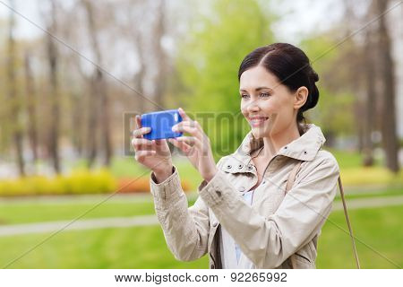 drinks, leisure, technology and people concept - smiling woman taking picture with smartphone in park