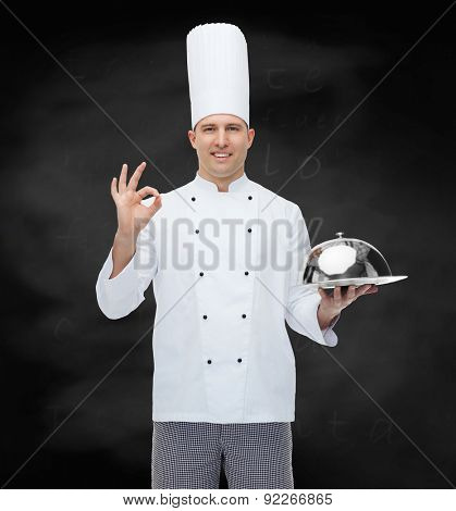 cooking, profession, gesture and people concept - happy male chef cook holding cloche and showing ok sign over black chalk board background