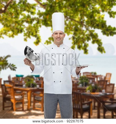 cooking, profession and people concept - happy male chef cook opening cloche cover over restaurant lounge on beach