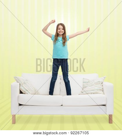 home, leisure, people and happiness concept - smiling little girl jumping and dancing on sofa over yellow striped background