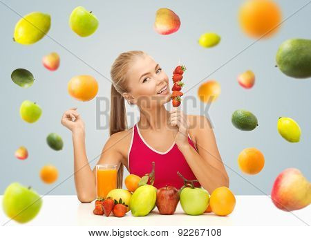 healthy eating, diet, detox, organic food and people concept - happy young woman with juice and fruits eating strawberries over gray background
