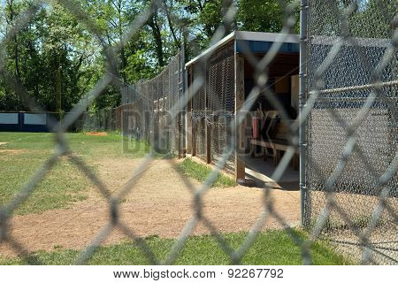 Baseball first base dugout and bullpen seen through chainlink fence