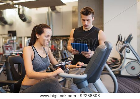 sport, fitness, lifestyle, technology and people concept - woman and trainer with tablet pc computer working out on exercise bike in gym