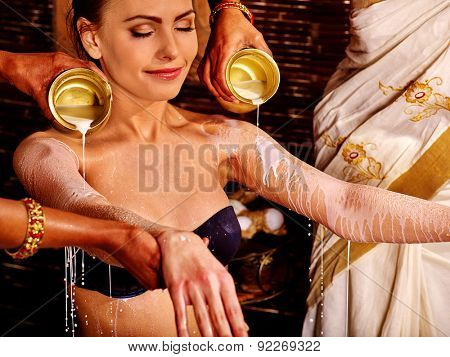 Woman having Ayurvedic spa treatment. Two masseuses are pouring milk.