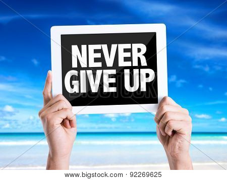 Tablet pc with text Never Give Up with beach background