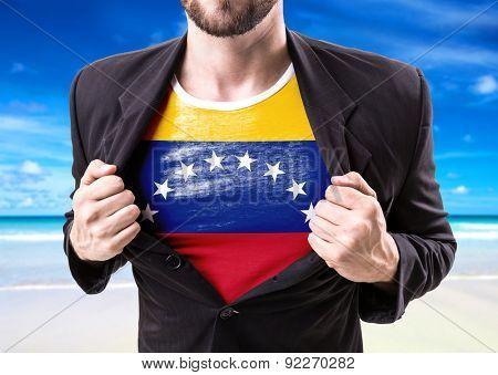 Businessman stretching suit with Venezuela flag on beach background
