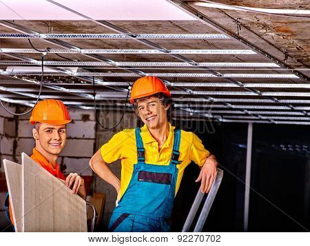Men in builder uniform installing suspended ceiling
