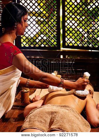 Woman having Ayurveda massage with herbal ball. Open window on background.