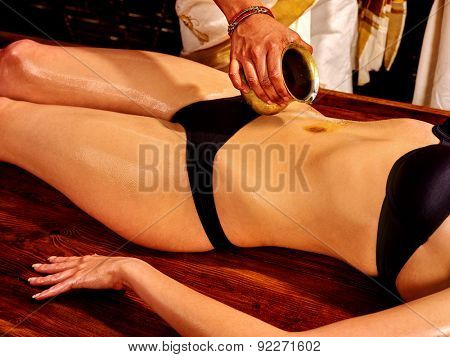Young woman having stomach Ayurveda spa treatment.