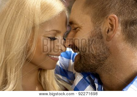 Portrait of romantic married couple together. Attractive blonde, smiling woman and stubbly handsome man.