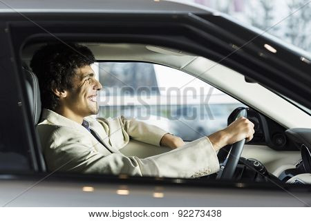 Handsome young man sitting in car in showroom