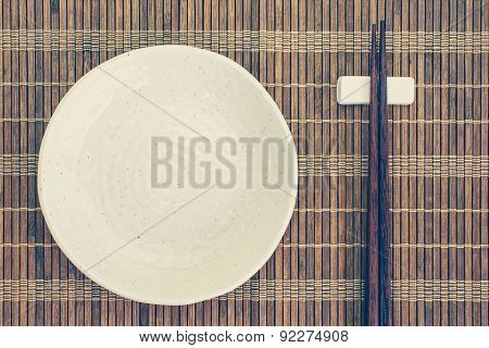White ceramic plate and wood chopsticks on bamboo mat