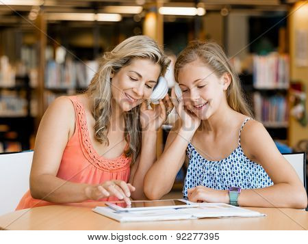 A teenage girl with headphones sitting in a library with her mum