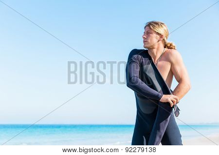 A young surfer putting on his wetsuit on the beach