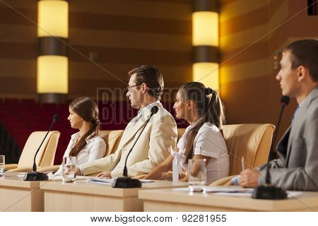 Young business people sitting at table in conference hall