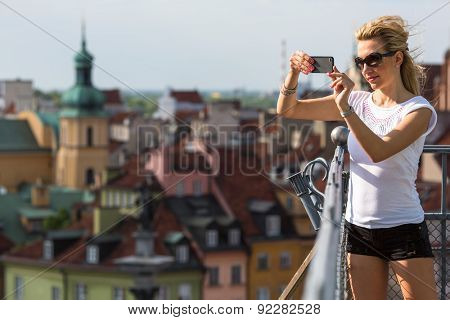 Young attractive girl photographs on smartphone Old European Town from top the observation tower.