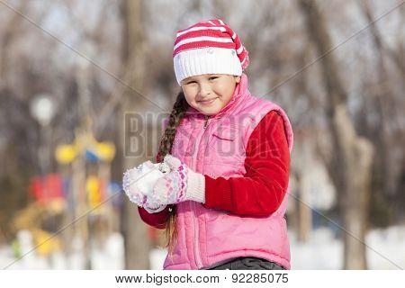 Cute girl of school age having fun in winter park