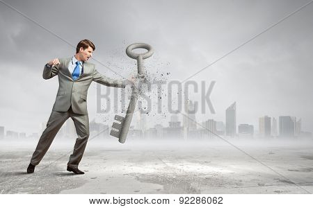 Young businesman crashing stone key with fist punch