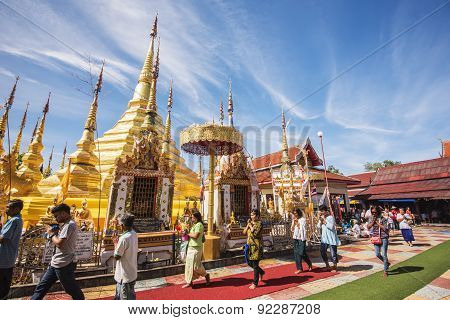 Buddhist people praying and walking around a golden pagoda.