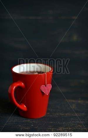Mug Of Tea And The Tea Bag With A Heart On A Dark Wooden Surface